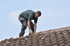 Arbeiter, der Dachplatten und Kantenfliesen ersetzt Stockbilder