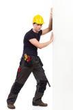 Arbeiter, der die Wand drückt Stockbild