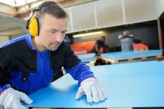 Arbeiter, der Kennzeichen auf blauem Plattenmaterial betrachtet Lizenzfreies Stockbild