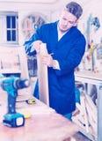 Arbeiter, der Spanplatte für Arbeit vorbereitet Stockbilder