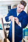 Arbeiter, der Spanplatte für Arbeit vorbereitet Lizenzfreie Stockfotos