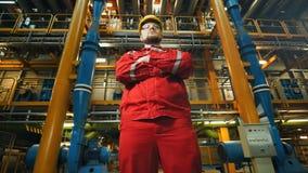 Arbeiter in der Uniform, die auf Industrieanlage aufwirft stock video