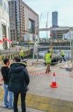 Arbeiter, die einen großen Stein mit tragbarer Hebemaschine bewegen stockfoto