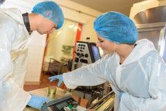 Arbeiter, die Metallzinn foodon Skalen in der Fabrik wiegen lizenzfreie stockfotografie