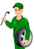 Arbeiter im Autoreparaturservice, der Rad und Schlüssel hält lizenzfreie abbildung