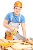 Arbeiter mit dem Sturzhelm, der hölzerne Diele mit einer Säge schneidet Stockfoto