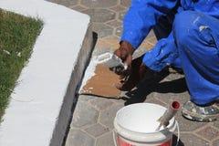 Arbeiter mit Farbentopf und Bürsten, die draußen malen Stockbild