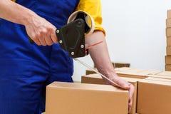 Arbeiter mit Packbandabroller Lizenzfreie Stockfotos