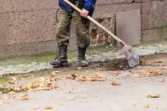Arbeiter säubert einen Abzugsgraben mit Schaufel des Bodens und Sand nahe dem Palast im Fall Stockfoto