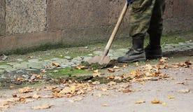 Arbeiter säubert einen Abzugsgraben mit Schaufel des Bodens und Sand nahe dem Palast im Fall Lizenzfreies Stockbild