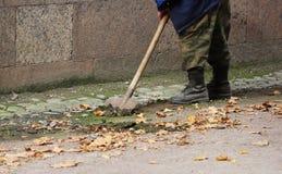 Arbeiter säubert einen Abzugsgraben mit Schaufel des Bodens und Sand nahe dem Palast im Fall Lizenzfreie Stockfotos