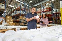Arbeiter und Manager, die Waren auf Fertigungsstraße überprüfen Stockbilder