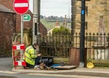 Arbeiterfestlegungs-Telefonleitung auf einer Waliser-Straße Stockfotos