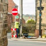 Arbeiterfestlegungs-Telefonleitung auf einer Waliser-Straße Stockbild