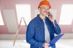 Arbeitersanwendung handlich auf der Baustelle Lizenzfreie Stockfotografie