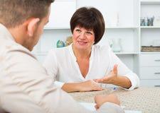 Arbeitgeber bespricht sich mit älterer Frau Stockfotografie