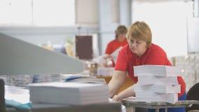 Arbeitnehmerin baut einen Stapel Papier in der Typografie auseinander stockbild