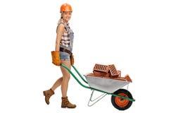 Arbeitnehmerin, die eine Schubkarre drückt Lizenzfreies Stockfoto