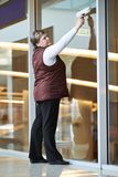Arbeitnehmerin, die Innenfenster säubert Stockbild