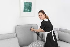 Arbeitnehmerin, die Schmutz vom Sofa mit Berufsstaubsauger, zuhause entfernt lizenzfreie stockfotografie