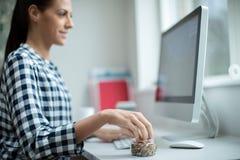 Arbeitnehmerin im Büro, das gesunden Imbiss von getrockneten Nüssen und von Samen isst stockfoto