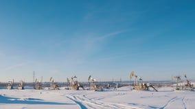 Arbeitsölpumpen auf dem Wintergebiet auf dem Hintergrund der Stadt Lizenzfreie Stockfotografie
