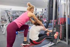 Arbeitsübung des persönlichen Eignungstrainers mit reifer Frau in der Turnhalle Gesundheitseignungssport-Alterskonzept stockbild