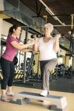 Arbeitsübung des persönlichen Trainers mit älterer Frau in der Turnhalle lizenzfreies stockbild
