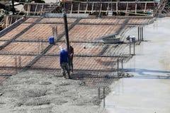 Arbeitsarbeit zwei, die flüssigen Beton von Betonmischer zu buil gießt Stockfoto