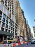 Arbeitsbereich, Crane Lifting Construction Material Above-Fußgänger, Manhattan, NYC, NY, USA Stockfoto