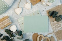 arbeitsbereich Hochzeitseinladungskarten, Handwerksumschläge, rosa und rote Rosen und Grünblätter auf weißem Hintergrund Lizenzfreies Stockfoto