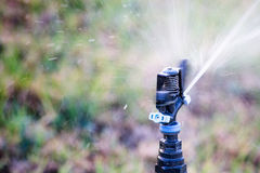 Arbeitsbewässerungsgras der berieselungsanlage Lizenzfreie Stockfotos