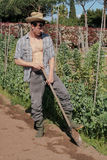Arbeitsboden des jungen Landwirts mit Schaufel Stockfotos