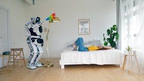 Arbeitscyborgstaub die Möbel während eine Frau, die auf einem Bett liegt stock video footage