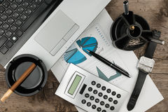 Arbeitsgeschäftsmannschreibtisch, -laptop, -zigarre und -diagramm als der Hintergrund Lizenzfreie Stockfotos