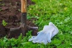 Arbeitshandschuhe einer Schaufel und ein Landwirt ` s mit einem grünen Gras in der Front und hinten gegraben herauf Boden Lizenzfreie Stockfotos