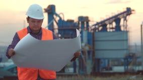 Arbeitsingenieur in einem Sturzhelm auf dem Hintergrund der Firma, die eine Zeichnung bei Sonnenuntergang hält stock video