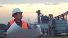 Arbeitsingenieur in einem Sturzhelm auf dem Hintergrund der Firma, die eine Zeichnung bei Sonnenuntergang hält stock video footage