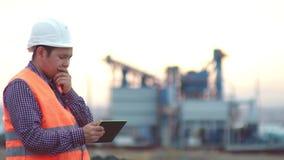 Arbeitsingenieur in einem Sturzhelm auf dem Hintergrund der Firma, die eine Zeichnung bei Sonnenuntergang hält stock footage