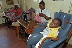 Arbeitskenyanfrau, behindertes Kind, Nairobi Stockbild