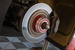 Arbeitskräfte überprüfen die hinteren Bremsen eines Supercar in der Garage stockfotografie