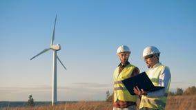 Arbeitskräfte überprüfen Windmühlen auf einem Gebiet und gehen Auswechselbares electririty, grünes Energiekonzept stock video footage