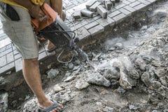 Arbeitskräfte benutzen elektrischen konkreten Unterbrecher Männliche Arbeitskraft, die Fahrstraßenoberfläche mit Jackhammer, dem  lizenzfreies stockfoto