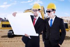 Arbeitskräfte betrachten Plan in den Baustellen Stockbilder