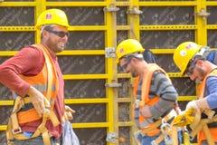 Arbeitskräfte in den Sturzhelmen auf der Baustelle Bauarbeiten lizenzfreies stockfoto