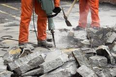 Arbeitskräfte an der Baustelle Asphalt demolierend stockfotografie