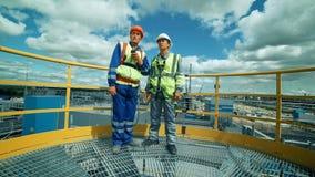 Arbeitskräfte in der Produktionsanlage als besprechendem Team, industrieller Szene im Hintergrund stock video footage