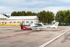 Arbeitskräfte, die Cessna 172 SP-Flugzeug auf Hangar verschieben Stockfoto