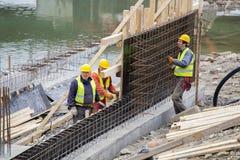 Arbeitskräfte, die an der Stützmauer, Rebar binden arbeiten lizenzfreie stockfotos