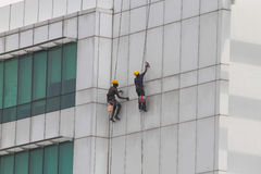 Arbeitskräfte, die ein mehrstöckiges Gebäude säubern oder malen Stockfoto